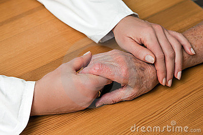Hands of a nurse and a former senior