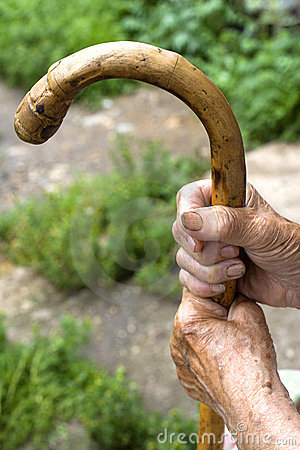 Hands of an old woman with a cane