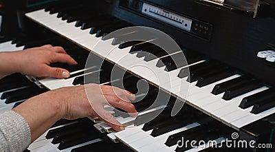 Hands on an organ keyboard