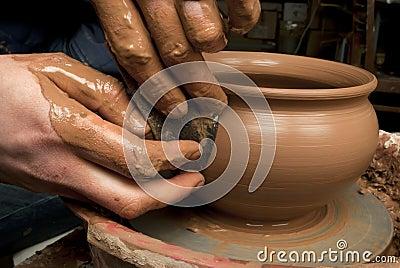 Hands of a potter, creating an earthen jar