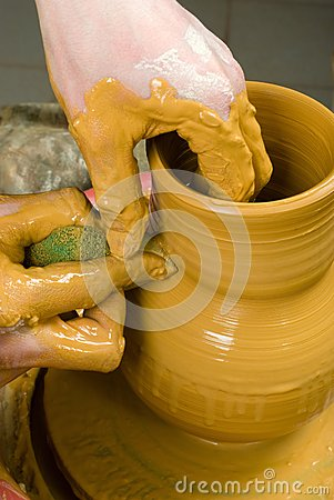 Hands of a potter, creating an earthen jar of yellow clay