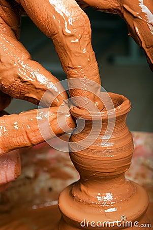 Hands of a potter, creating an little earthen jar