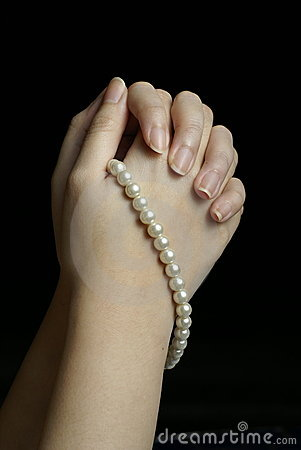 Hands in prayer with pearls
