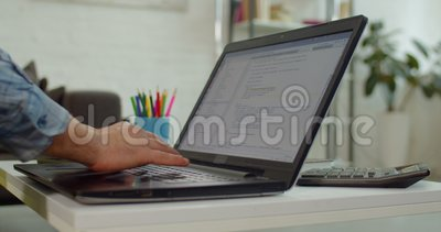 Hands of programmer working with computer in office. Close-up of male hands of freelance programmer typing new lines of HTML code on laptop while creating web stock video