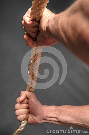 Hands pulling rope over dark background