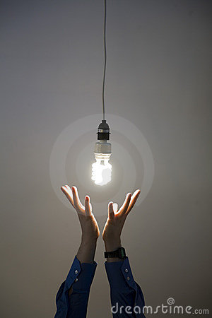 Hands reaching for light bulb