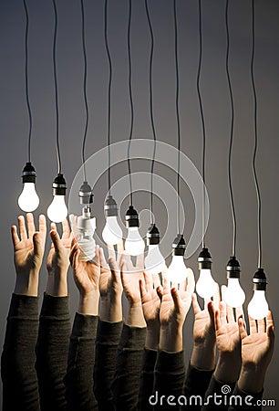 Hands reaching for light bulbs