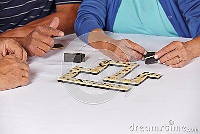Hands of seniors playing domino