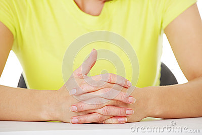 Hands on table with intertwined fingers