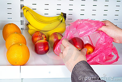 Hands take nectarines from store shelves