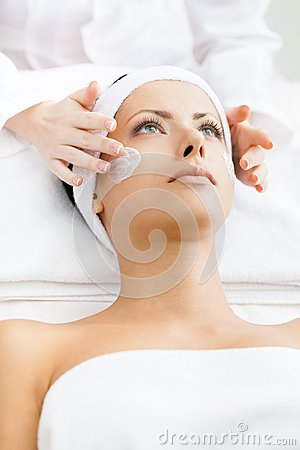 Hands of therapist apply cream to woman face
