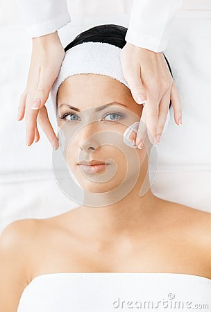 Hands of therapist apply cream to young woman face
