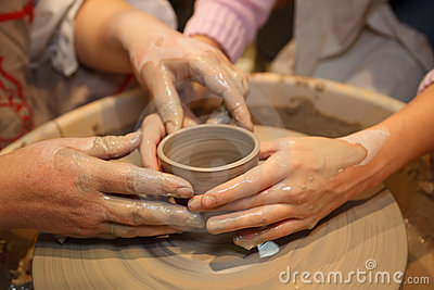Hands of two people create pot on potter s wheel