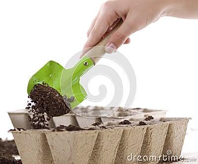 Hands Using Shovel Placing Soil into Compost Pots