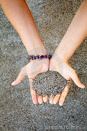 Hands with wet sand