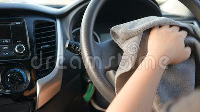 Hands of woman using microfiber fabric to clean up steering wheel interior of SUV car stock video
