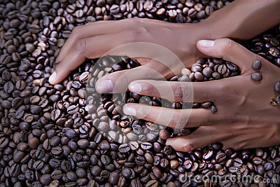 Hands of a young woman and coffee beans