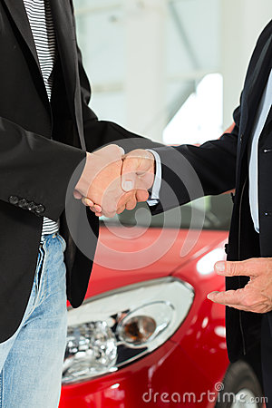 Handshake of two men in suits with a red car