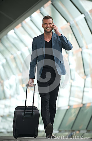 Handsom Man Walking in City with Cell and Suitcase