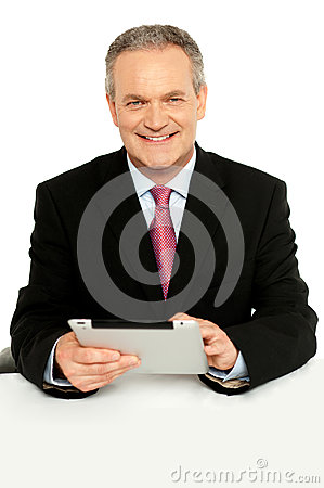 Handsome aged business male using tablet pc