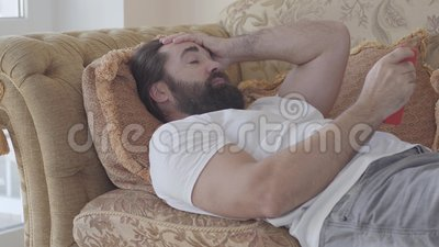 Handsome bearded man lying on the sofa checking cell phone. Guy is angry, he throws away smartphone. Receiving bad news. Bearded man lying on the sofa checking stock video footage