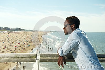 Handsome black man with sunglasses relaxing at the beach