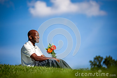 Handsome black man waiting for date with flowers