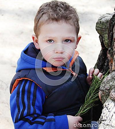 Handsome boy standing near tree.