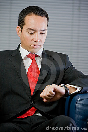 Handsome business man looking at his watch