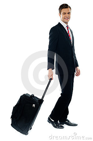 Handsome businessman dragging trolley bag