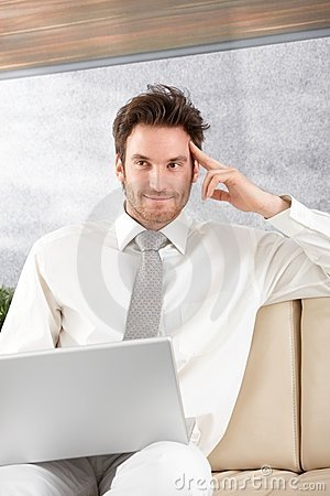 Handsome businessman with laptop smiling