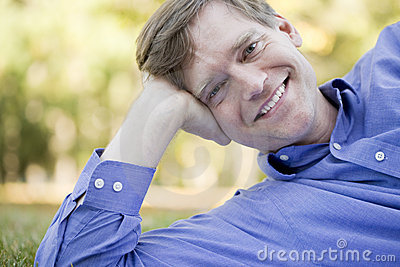 Handsome businessman relaxing on grass