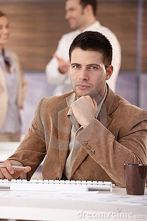 Handsome businessman sitting at desk