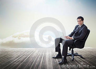 Handsome businessman sitting on a swivel chair and using his lap