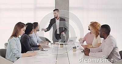 Handsome caucasian ceo executive presenta una nuova strategia commerciale ai suoi colleghi in sala conferenze Capo maschio stock footage