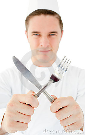 Handsome cook holding cutlery