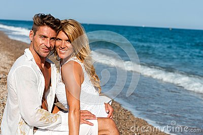 Handsome couple in white on beach.