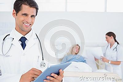 Handsome doctor using digital tablet