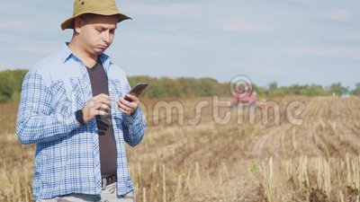Handsome farmer with smartphone standing in field sunflower with combine harvester in background. Concept modern. Technology application in agricultural growing stock video