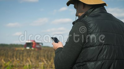 Handsome farmer with smartphone standing in field sunflower with combine harvester in background. Concept modern. Technology application in agricultural growing stock footage