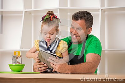 Handsome father and cute little daughter cooking
