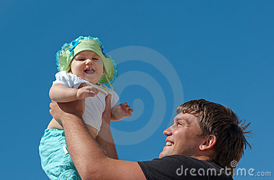 Handsome father holding his cute daughter