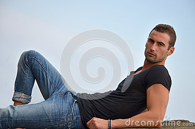 Handsome and fit young man laying on a rock
