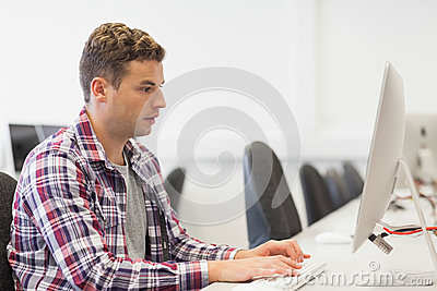 Handsome focused student working in computer room