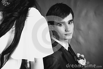Handsome groom leaning on brides back