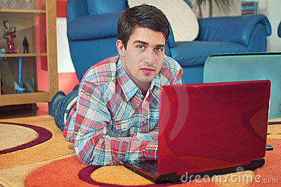 Handsome guy using laptop while lying on a floor