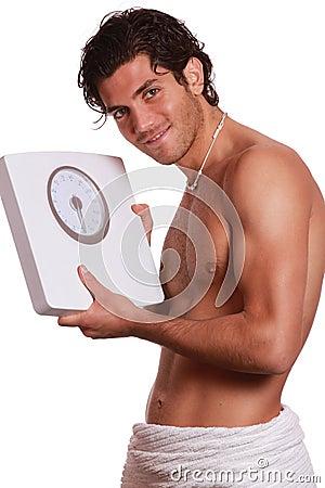 Handsome happy man and weighting machine