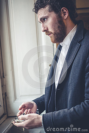 Handsome hipster elegant man with pocket watch