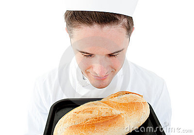 Handsome male cook smelling at a fresh bread