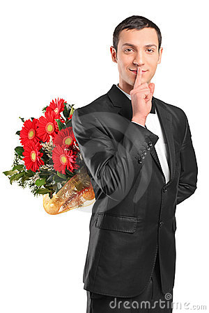 Handsome male hiding a bouquet of flowers